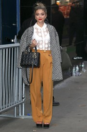 Sarah Hyland teamed her coat with a pair of high-waisted mustard slacks and a sheer white blouse.
