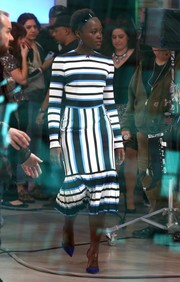 Lupita Nyong'o appeared on 'Good Morning America' wearing a chic Dolce & Gabbana dress featuring bold stripes and a pleated hem.