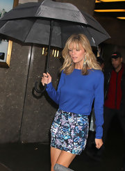 Brooklyn shielded herself from the rain with a classic black umbrella.