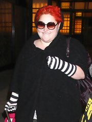 Beth is rocker chic with flaming red hair and big shades.