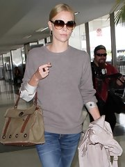 Charlize traveled in style wearing a crewneck sweater over a silky long-sleeve blouse.