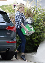 Charlize Theron geared up to watch the Super Bowl in a loose plaid button up and cropped skinny jeans.