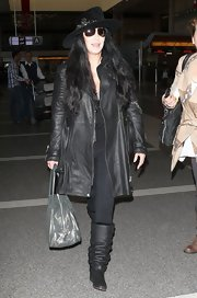 Cher cozied up in a pair of slouchy black boots and a leather coat during a flight out of LAX.