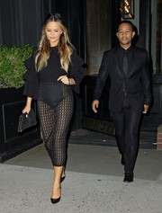Chrissy Teigen contrasted her revealing skirt with a modest black ruffle top by Asilio.