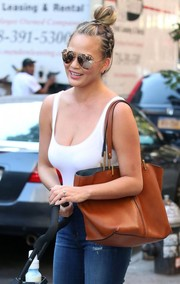 Chrissy Teigen was one hot mama pushing a stroller in a low-cut white bodysuit by Wolford!