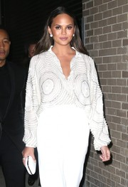 Chrissy Teigen headed out in New York City sporting an all-white hard-case clutch, blouse, and pants combo.