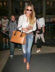 Chrissy Teigen looked sweet and ladylike in an embroidered silk chiffon blouse by Rebecca Taylor as she arrived on a flight at LAX.