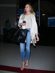 Chrissy Teigen showed off her supermodel legs in a pair of tight ripped jeans while making her way through LAX.