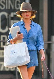 Chrissy Teigen teamed a walker hat with a denim romper for her breezy-chic strolling get-up.