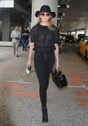 Chrissy Teigen completed her all-black airport look with a pair of suede ankle boots.