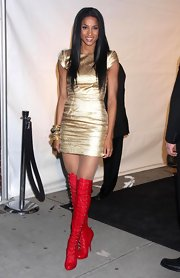 "Ciara looks like a Christmas ornament in this metallic gold mini and these bold red ""Alta Fifre Corset Boots""."