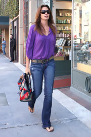 Cindy Crawford kept her street style relaxed in a loose purple peasant blouse and flared jeans.
