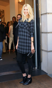 "To present her new collection in Berlin, Claudia Schiffer wore a plaid tunic with a pair of ""Major"" high-rise leggings with an ankle-zip. Pointy ankle boots completed her ensemble."