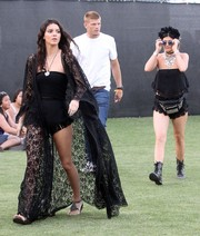 Kendall Jenner looked dramatic in a long black lace robe layered over a tube top and fringed shorts during Coachella.