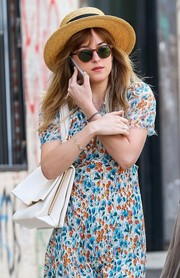 Dakota Johnson looked very summery in a straw hat and a floral dress while out and about in New York City.