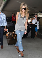 Though ruggedly dressed, Delta Goodrem traveled in style with a Louis Vuitton rollerboard and duffel bag.