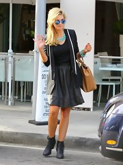 Delta Goodrem added a feminine touch to her structured look with a flared black mini skirt.
