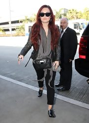 Demi Lovato wore her wavy tresses casually flowing while arriving at LAX.