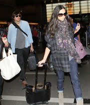 Demi Moore bundled up for her flight in a floral print scarf and plaid coat.