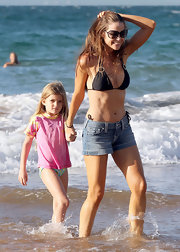Denise Richards had some fun in the sand and waves in a black bikini top and jean shorts.