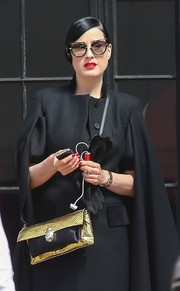 Dita Von Teese accessorized with a metallic gold shoulder bag for a bit of shine to her all-black outfit.