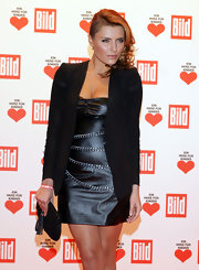 Sophia wears a little black leather dress with heavy chains.