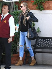 Emily VanCamp accessorized with a classic black hobo bag.