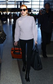 Emma Roberts styled her airport look with an oversized black tote by Balenciaga.