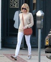 A brown leather shoulder bag by Disney x Coach rounded out Emma Roberts' daytime ensemble.