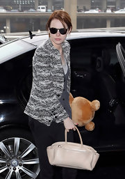 Emma Stone was accompanied by her polished ivory leather tote and a cuddly teddy bear at the airport.