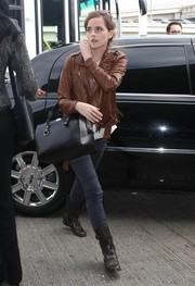 Emma Watson toughened up in a brown 3.1 Phillip Lim leather moto jacket for a flight out of LAX.