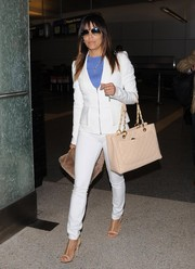 Eva Longoria teamed her suit with nude accessories, including a stylish quilted tote by Chanel.
