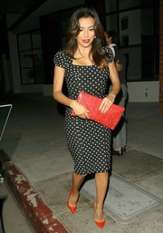 Eva Longoria added an extra pop of red with a snakeskin envelope clutch.