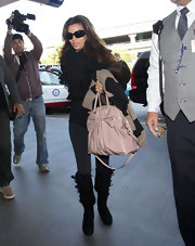 Eva Longoria traveled in style in black knee-high boots with buckled detailing.