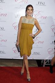 Teri looked chic in a mustard-colored cocktail dress with a draped skirt and a beaded, inset neckline.