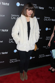 Rose Byrne bundled up in a white fur jacket and brown suede ankle boots.