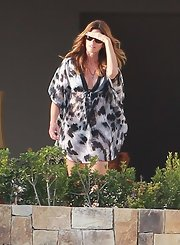 Cindy Crawford hangs out in Cabo wearing a pair of sunglasses and a boldly printed tunic.