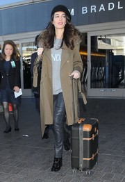 Amal Clooney made a stylish arrival at LAX wearing a tan fur-collar trenchcoat by Adam Lippes.