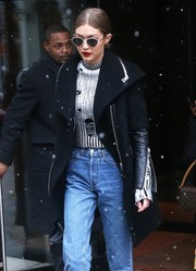 Gigi Hadid's Le Specs sunglasses put an ultra-modern spin on the classic cat-eye shape that she wore with a Zoe Jordan sweater.