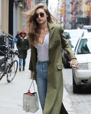 Gigi Hadid layered a white henley shirt by Rails under a green wool coat for a day out in New York City.