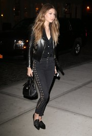 Gigi Hadid went for a rocker edge in a studded black moto jacket by Versace for a night out in New York City.