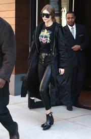 Gigi Hadid cut a bold figure in a black-on-black duster and leather pants combo while out in New York City.