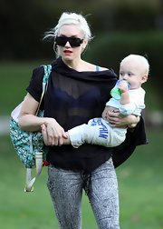 "Gwen shows her love for her handbag line by carrying the ""Raddest Panda"" diaper bag. The color is aqua blue with panda bears. This is a bag that can fits all she can carry, but matches her top. Gwen is a mom with style!"