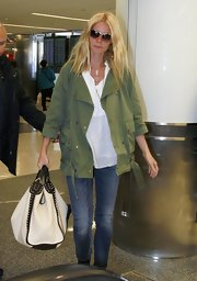 Gwyneth Paltrow chose a white straw bag with black leather trim and studs for her carry-all while traveling.