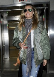Heidi Klum paired a printed scarf with a bomber jacket for a flight to LAX.