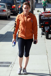 Hilary is ready for the gym in an orange track jacket.