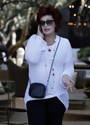 Sharon Osbourne swung a leather cross-body bag as she shopped with her family in West Hollywood.