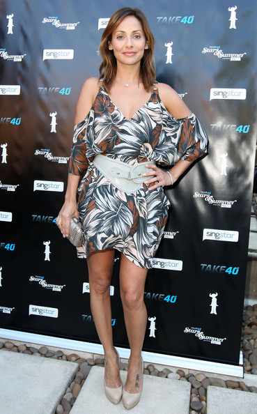 Natalie Imbruglia wears a floral print dress with shoulder cut outs and a white leather belt for a Summer Party in Australia.