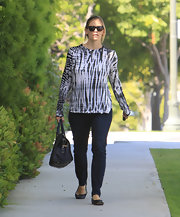 Jennifer keeps her street style simple in loose knit top with vibrant striped pattern.