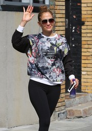 Jennifer Lopez was spotted outside her apartment wearing designer shield sunglasses and a sporty outfit.